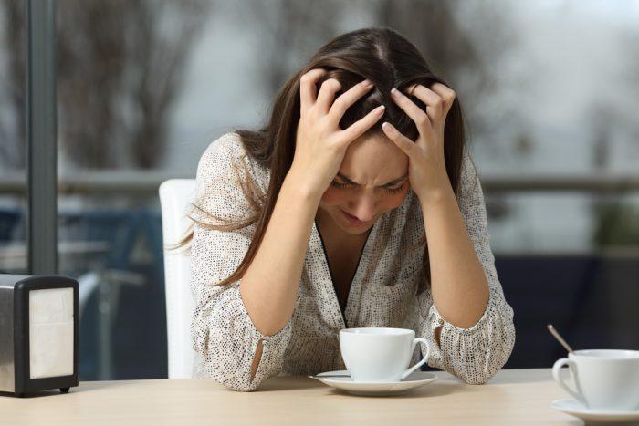 Девушка сидит за столом перед чашкой и держится за голову