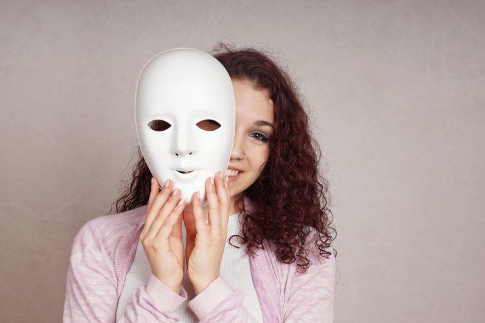 Девушка в рубашке держит маску