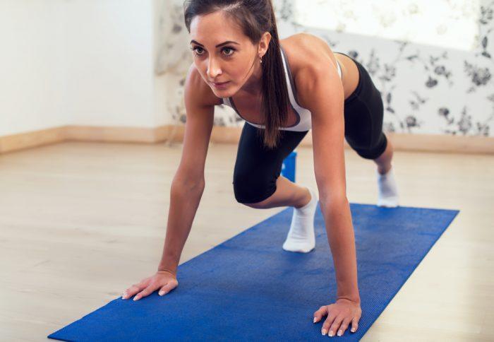 Стройная девушка делает упражнения на голубом мате, глядя прямо вперед