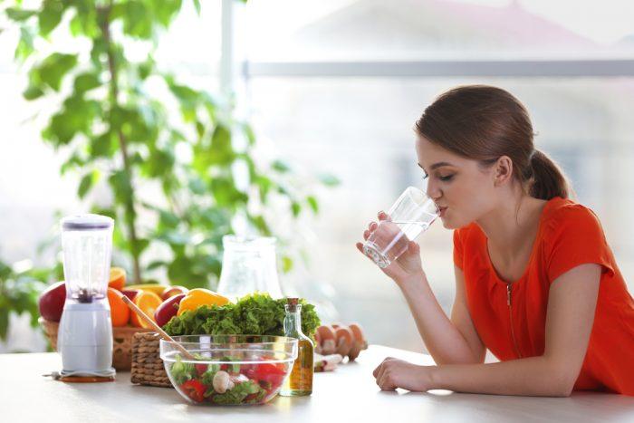 Девушка сидит за столом с салатом и пьет воду