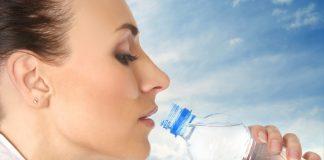 Девушка пьет воду из бутилки