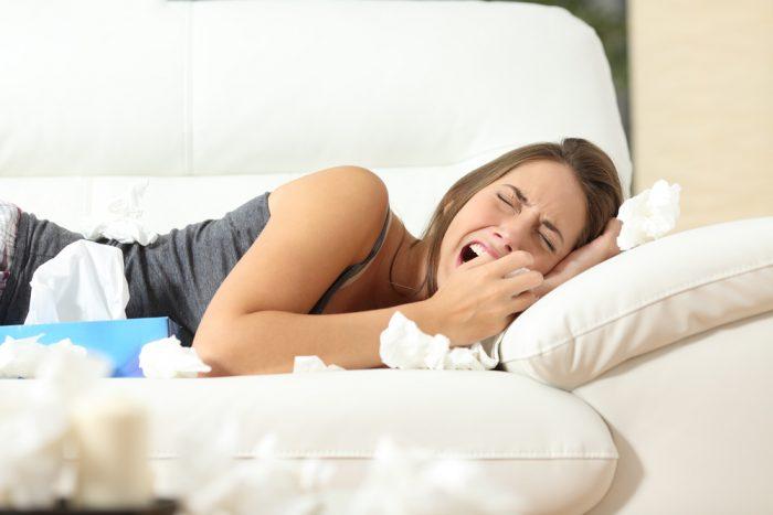 Девушка плачет на диване в салфетках