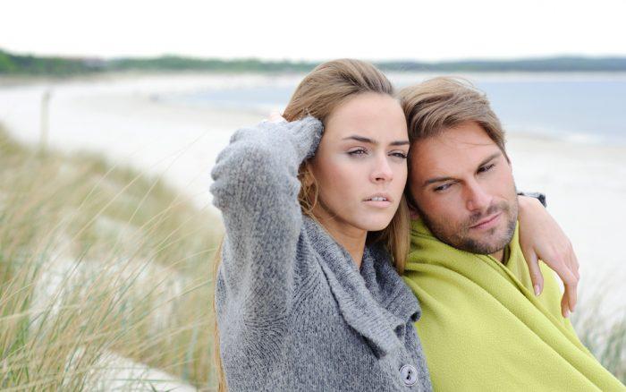 Красивая девушка в серой кофте сидит рядом с мужчиной