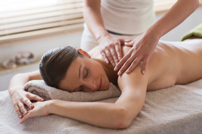 Девушке с обнаженной спиной делают массаж