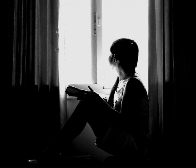 Черно-белое фото девушки сидящей на полу и смотревшей в окно