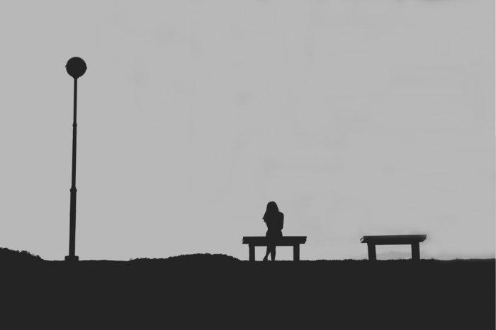 Черно-белое фото девушки сидящей на лавочке