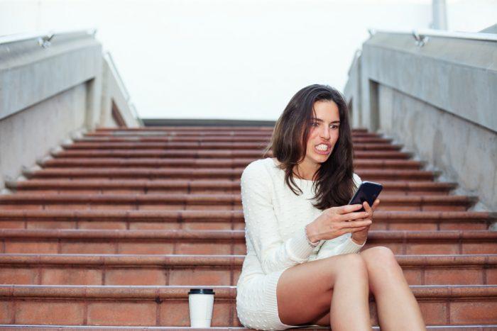 Девушка сидит на ступеньках с телефоном и кофе