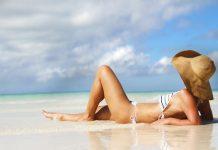 Девушка в соломенной шляпке лежит на берегу моря