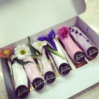 6 розовых и белых эклеров в коробке с цветами