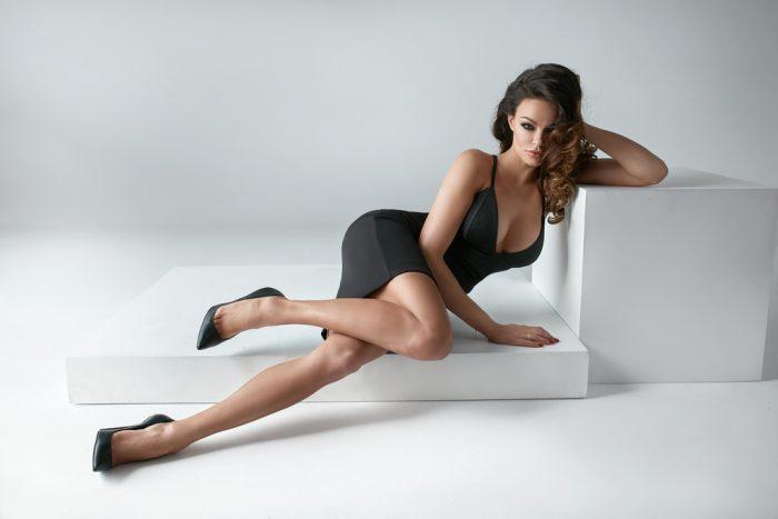 Красивая девушка в черном платье и туфлях на белом диване