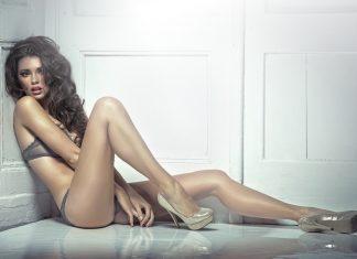Красивая девушка в белье и туфлях сидит на полу