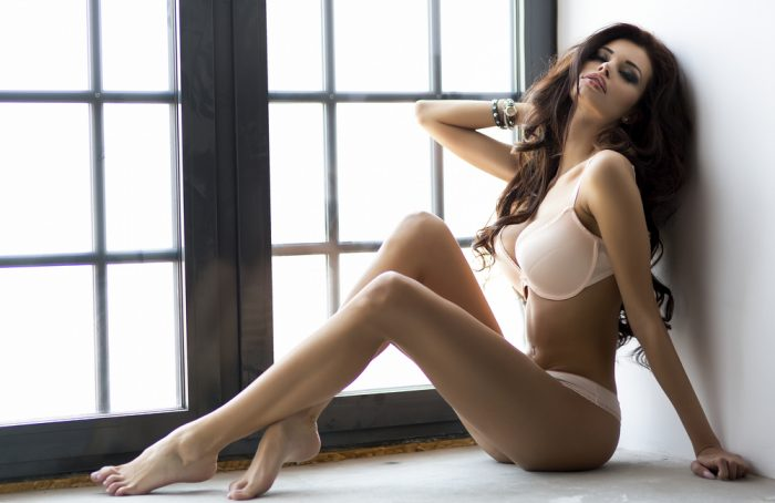 Красивая девушка сидит на полу в белом белье