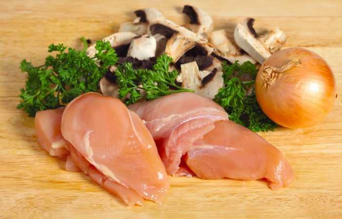 Ингредиенты: сырые куриные грудки,грибы,лук и петрушка на разделочной доске
