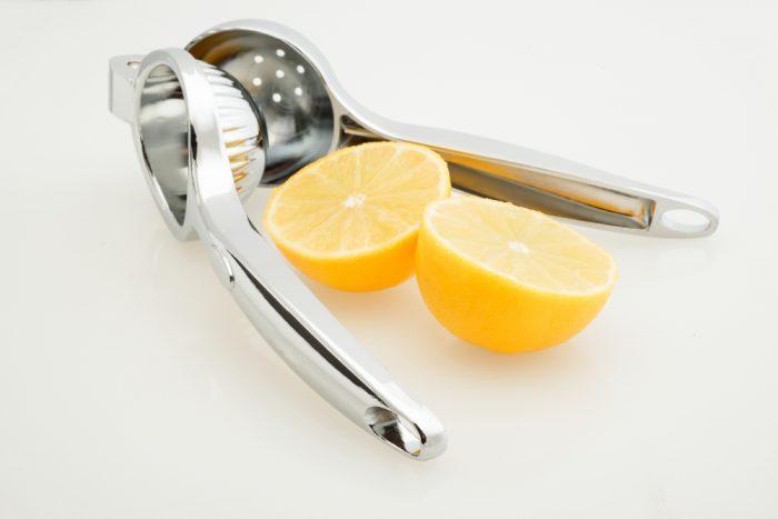пресс для лимона и две половины лимона