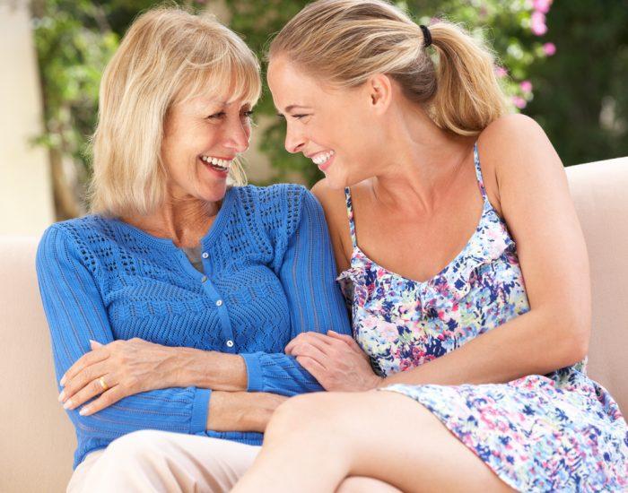 Мама с дочкой сидят и смеются