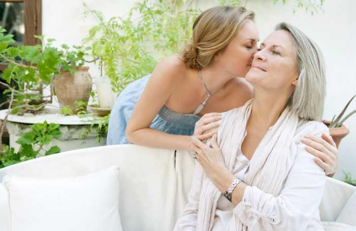 Дочка целует маму в щеку