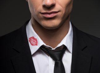 Мужчина с следом помады на белом воротнике рубашки