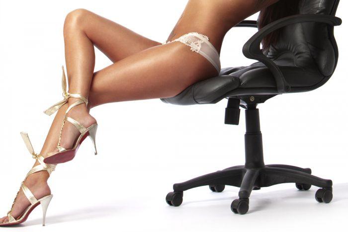 Девушка в белье и золотых босоножках сидит в черном кресле