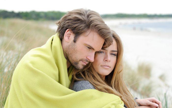 Парень в зеленой накидке обнял девушку