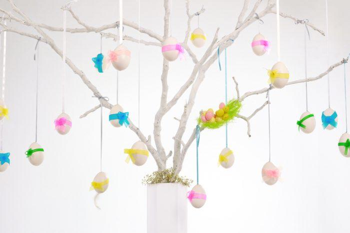 Пасхальные яйца висят на лентах на ветках дерева