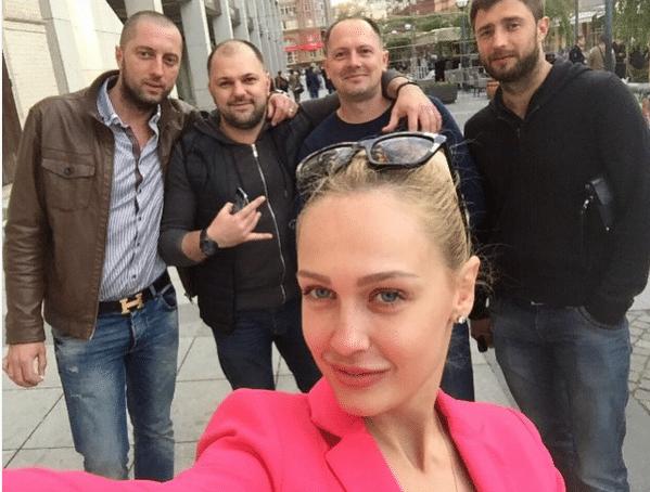 Снежана Задорожняя участница шоу Холостяк в розовом пиджаке фотографирует себя на фоне мужчин