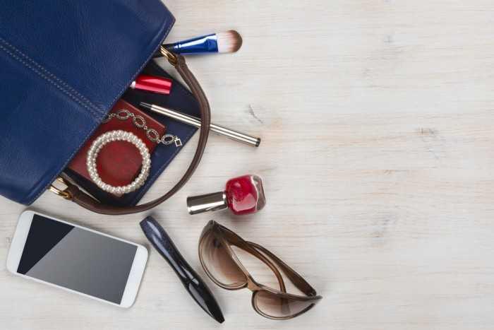 Содержимое женской сумочки на деревянном столе