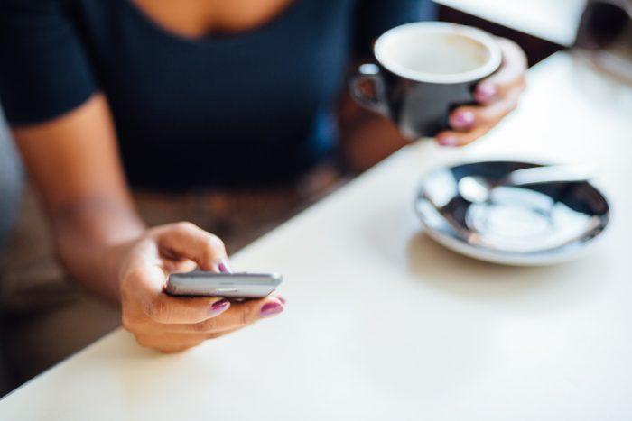 За столом с чашкой кофе держит телефон