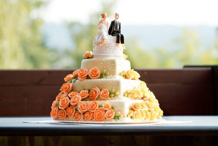 Свадебный торт в оранжевых цветах и с фигурками жениха и невесты