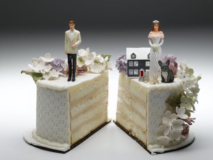 Разрезанный белый свадебный торт с фигурками жениха и невесты