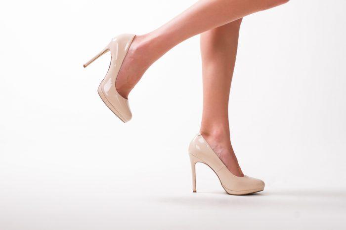 Женские ножки в бежевых туфлях на каблуке