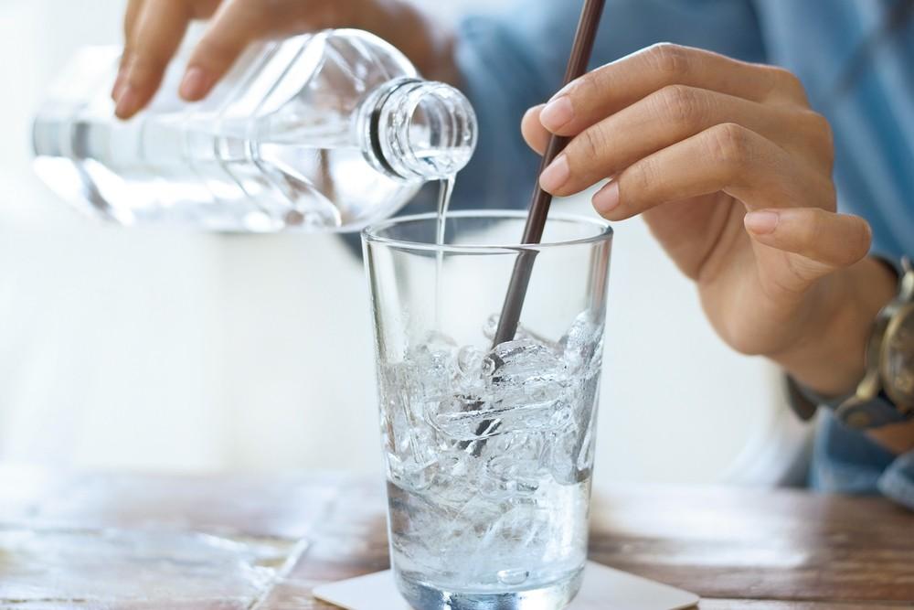 Наливают воду с бутылки в стакан со льдом