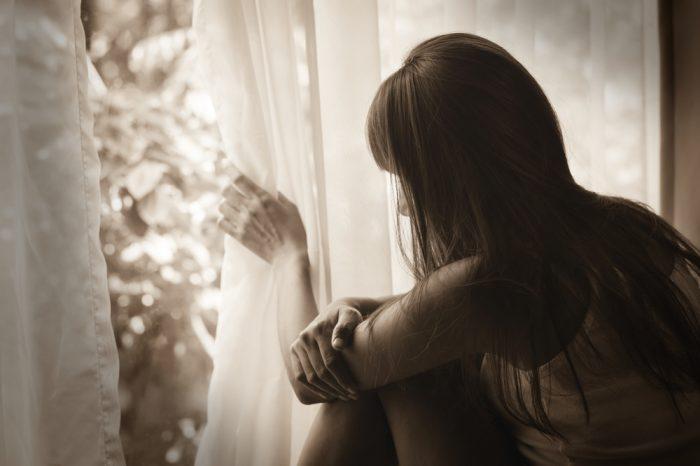 Девушка держит штору и смотрит в окно