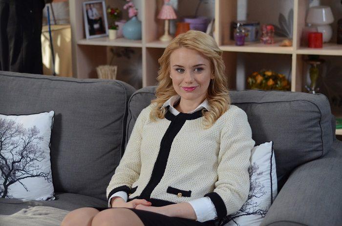 Алена Алымова, звезда скетчкома Коли ми вдома, сидит на диване в белом пиджаке с черными вставками
