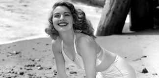 Ава Гарднер в белом шелковом купальнике сидит на песке