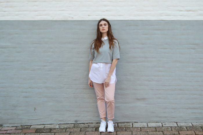 Девушка в белых кроссовках и кремовых брюках