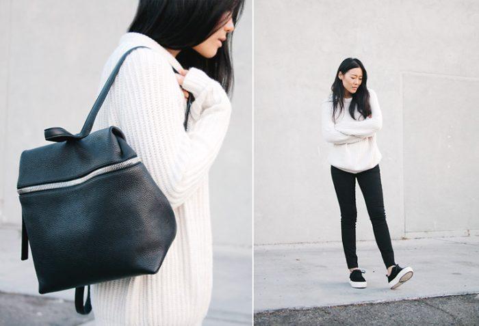 девушка в черных брюках, белом свитере и с черным рюкзаком