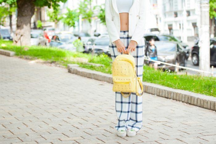 Девушка держит в курах желтый рюкзак