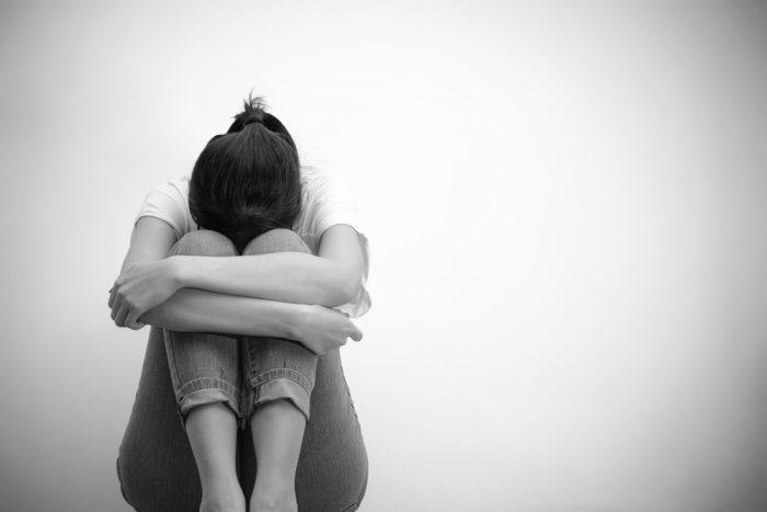 Девушка обняла руками колени и плачет