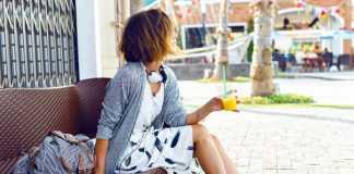 Девушка сидит с соком в белом платье, серой кофте и в мокасинах