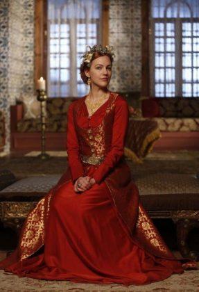 Девушка сидит в красном платье и в короне