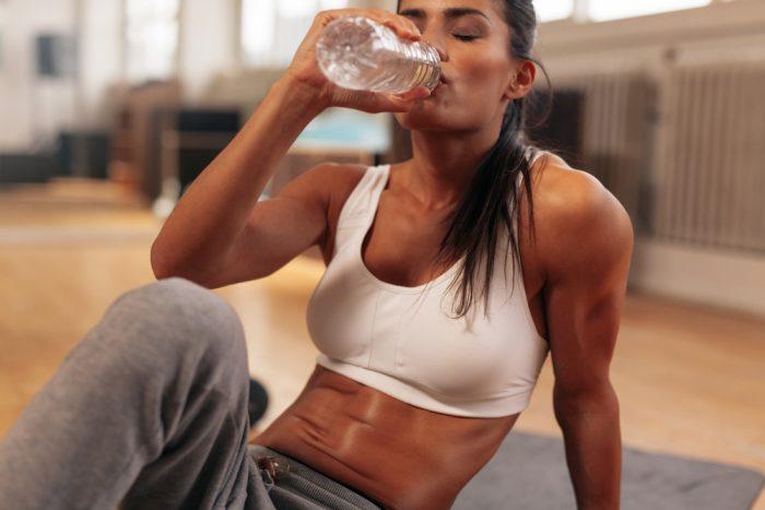 Девушка в белом топике пьет воду из бутылки