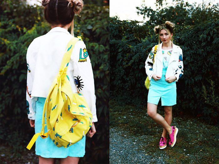Девушка в бирюзовой юбке,белой ветровке с желтым рюкзаком