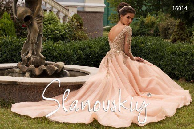 Девушка сидит на траве в бальном платье
