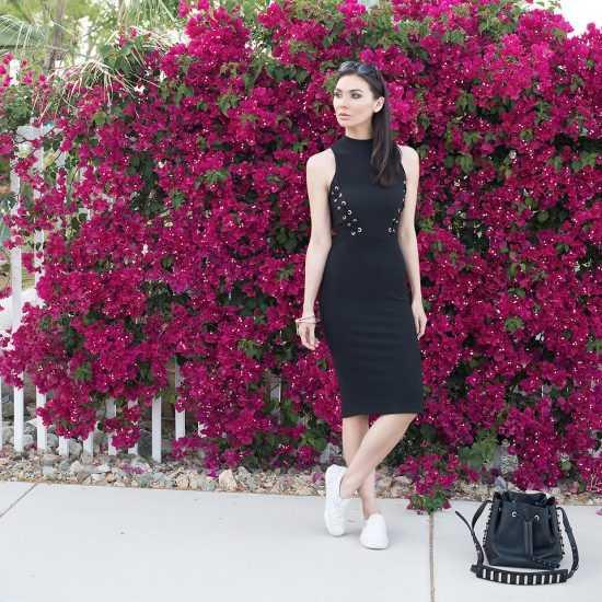 Девушка в черном платье и в белых слипонах