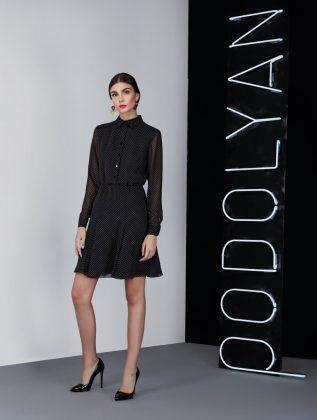 Девушка в деловом черном платье с рукавами
