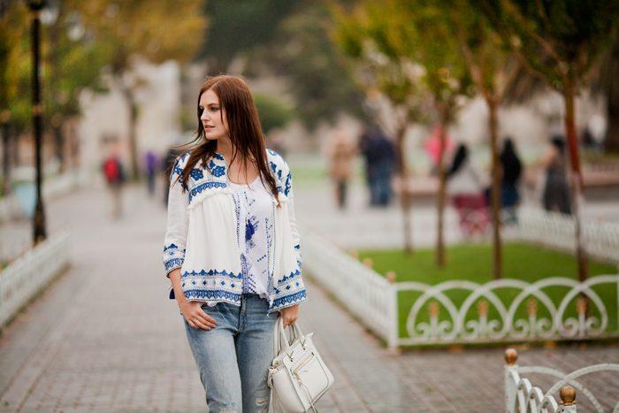 Девушка идет по улице в джинсах, с белой сумкой и в белой вышиванке с голубой вышивкой
