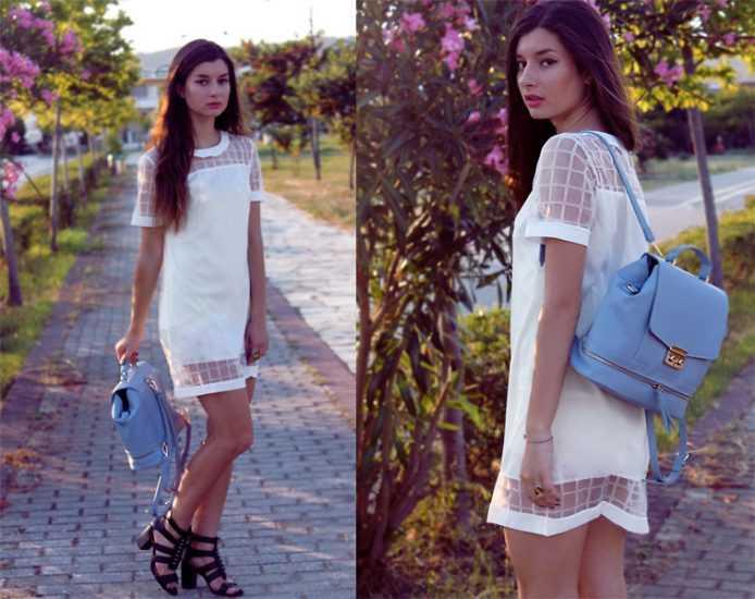Девушка в коротком белом платье с голубым рюкзаком