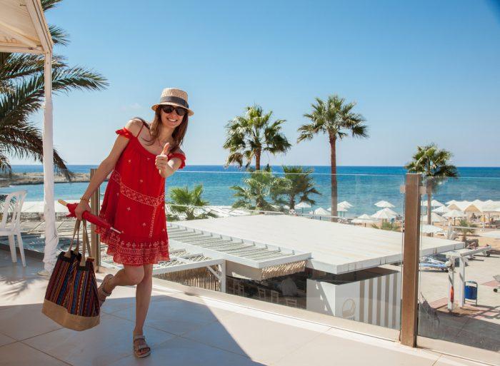Девушка в красном платье с открытыми плечами с сумкой и в шляпке на пляже