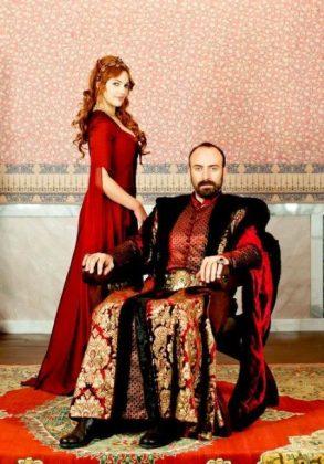 Девушка в красном платье стоит возле сидящего мужчины