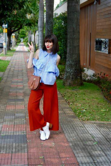 Девушка в красных брюках и голубой кофте с открытыми плечами